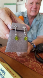 Steve Kanold holding diamond/peridot earrings